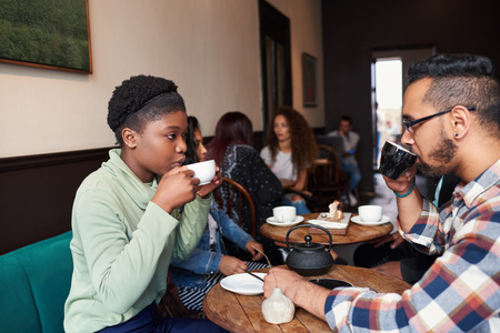 Multiethnic young couple talking over drinks in a cafe Stock Photo