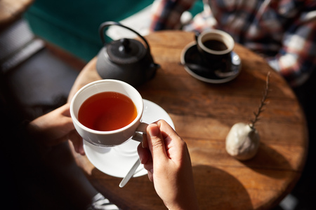 Woman about to drink tea while sitting in a cafe