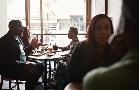 Group of diverse people sitting at tables in a cafe Stok Fotoğraf - 120258184