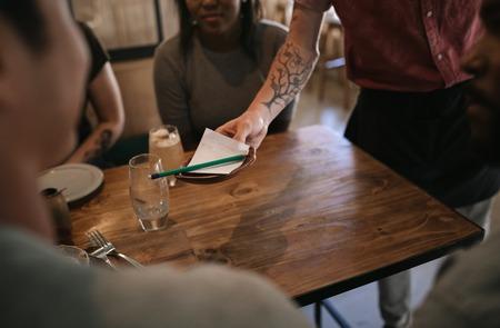 Ober overhandigt de rekening aan klanten in een bar
