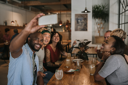 Group of smiling friends taking selfies together in a bar Stockfoto