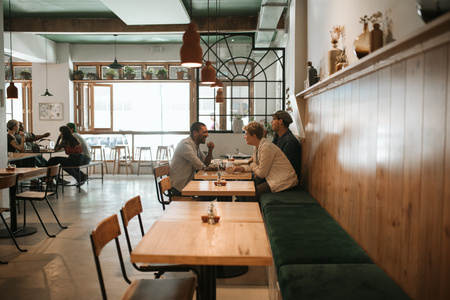 Diverse group of friends having lunch together in a bistro