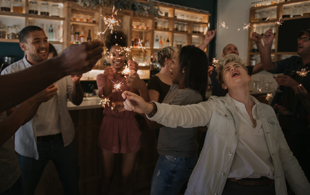 Young friends laughing and celebrating with sparklers in a bar Stock Photo
