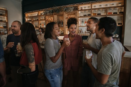 Diverse young friends enjoying an evening in a pub together