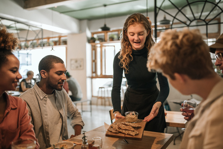 Smiling waitress bringing food to a table of customers