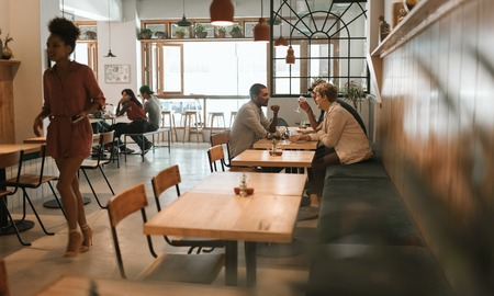 Friends talking together over drinks and lunch in a bistro
