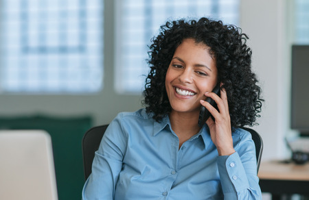 Mature businesswoman sitting at her desk talking on a cellphone