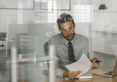 Content businessman sitting at work reviewing written ideas