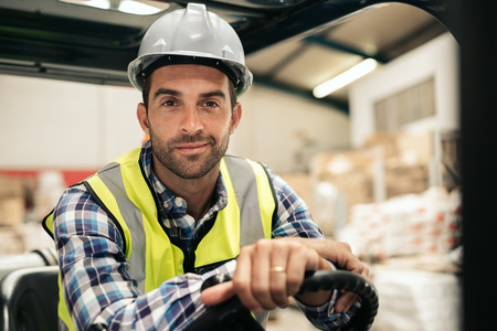 Smiling warehouse worker sitting in a forklift Stock fotó