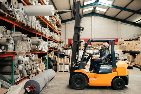 Forklift driver carefully moving stock around a large warehouse Imagens