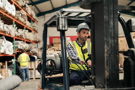 Forklift driver moving stock on the floor of a warehouse