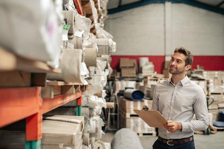 Gestionnaire d'entrepôt souriant à l'aide d'un presse-papiers tout en faisant l'inventaire Banque d'images