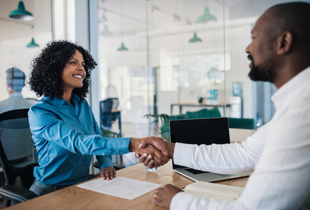 Smiling manager shaking hands with a woman after an interview