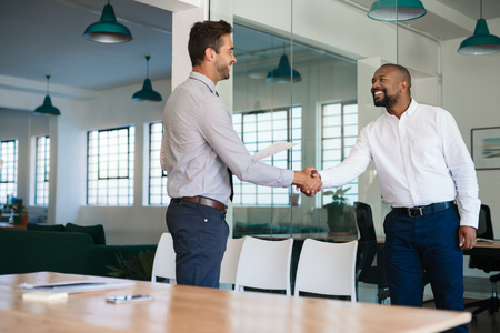 Smiling manager congratulating a job applicant after an interview Stock Photo