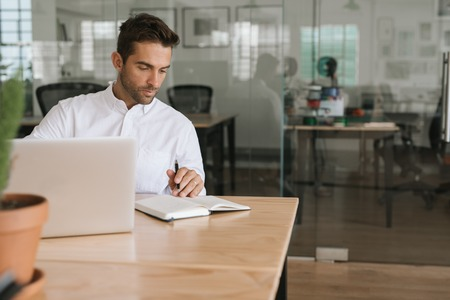 Young businessman working on a laptop and writing down notes