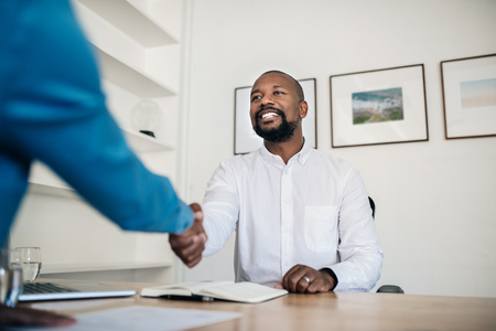 Smiling manager shaking hands with an employee in his office
