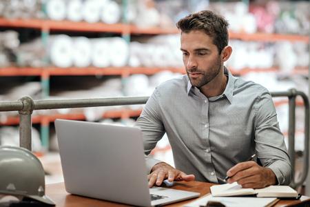 Lagerleiter macht sich Notizen und prüft Bestellungen mit einem Laptop Standard-Bild