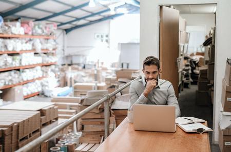 Manager die online werkt terwijl hij in een magazijnkantoor zit