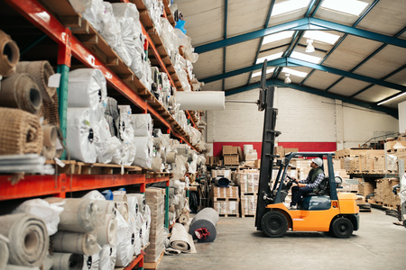 Forklift driver moving stock from shelves around a large warehouse
