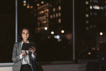 Businesswoman using a tablet in her office in the evening