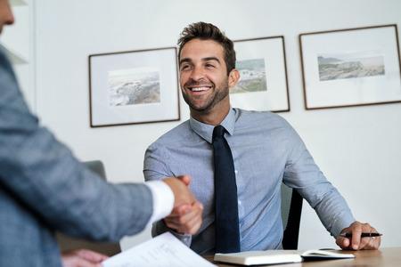 Manager sitzt an seinem Schreibtisch und schüttelt einem Mitarbeiter die Hand