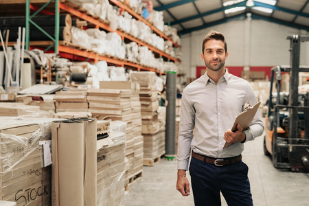 Smiling manager standing in his warehouse with a clipboard Stock fotó