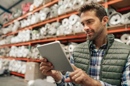 Smiling warehouse worker using a digital tablet to trace stock Standard-Bild - 125163546