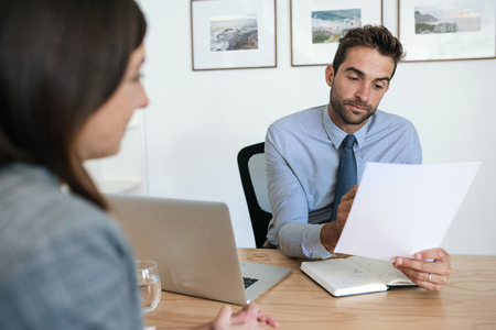Office manager reading a resume during an interview Stockfoto