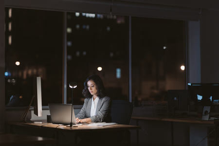 Giovane donna d'affari che lavora online in un ufficio buio di notte Archivio Fotografico