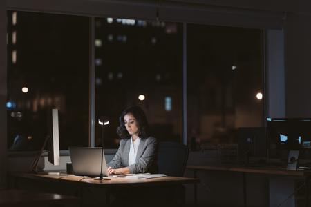 Joven empresaria trabajando en línea en una oficina oscura por la noche Foto de archivo