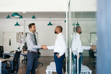 Two smiling businessmen shaking hands together after an office meeting