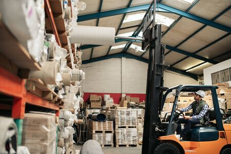 Forklift driver taking stock off shelves in a large warehouse