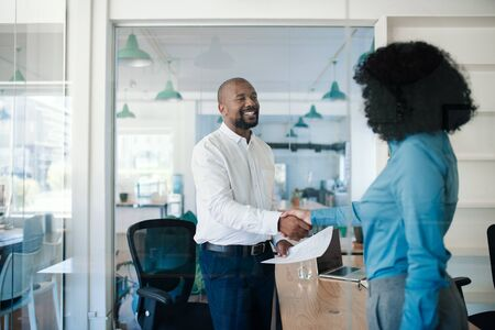 Smiling manager welcoming a new employee to the office