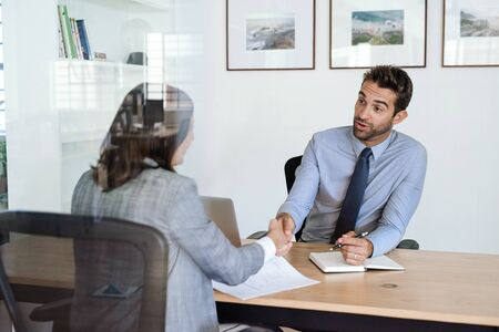 Manager shaking hands with an employee at his office desk Stock Photo