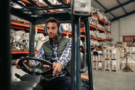 Forklift driver working on the floor of a warehouse