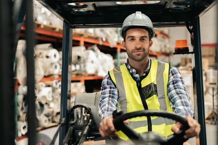 Smiling forklift driver moving stock on a warehouse floor Stock fotó