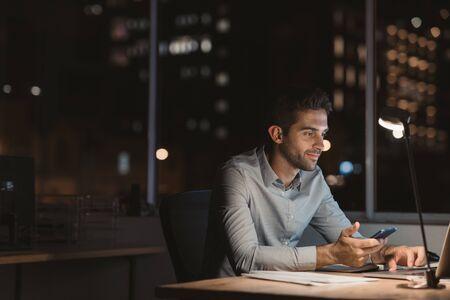 Joven empresario trabajando horas extras en su escritorio de oficina