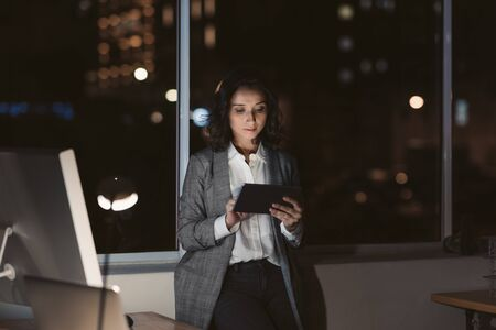 Young businesswoman using a tablet in her office at night