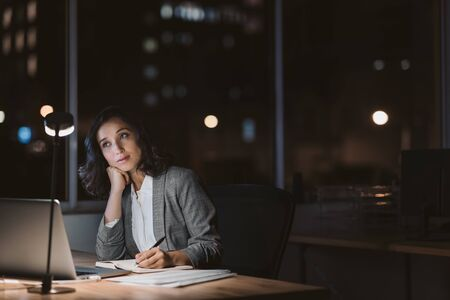 Businesswoman looking bored while working overtime at her office desk Imagens