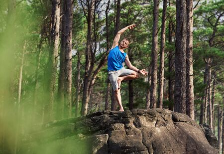 Fit man doing the bending tree pose in a forest