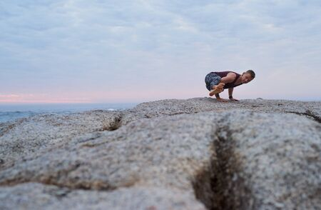 Fit man doing the eight angle pose by the ocean Stockfoto
