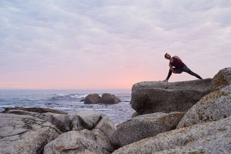 Man doing the eight angle pose on a rocky coastline