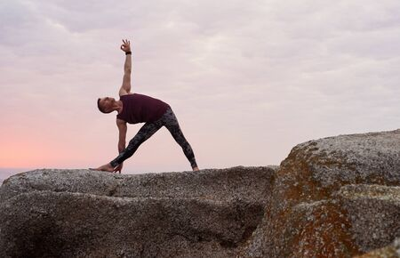 Man doing the triangle pose on some rocks at dusk Stockfoto