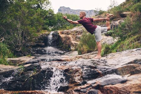 Fit man doing the dancer pose by a waterfall