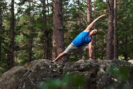 Man doing the extending side angle pose in a forest Stockfoto