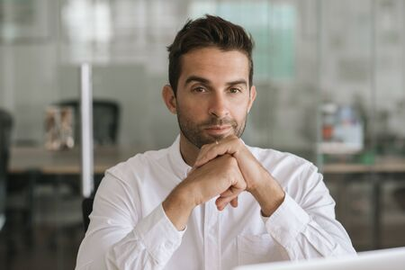 Focused young businessman sitting alone in a modern office