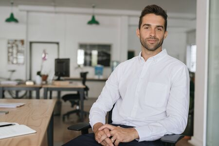 Confident young businessman sitting alone in a large modern office