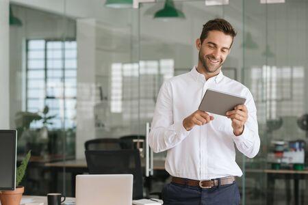 Uśmiechnięty biznesmen korzystający z tabletu w dużym, nowoczesnym biurze