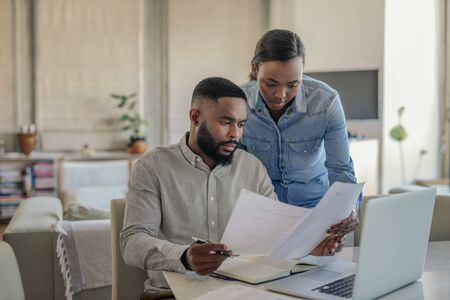 Young African American couple doing online banking at home