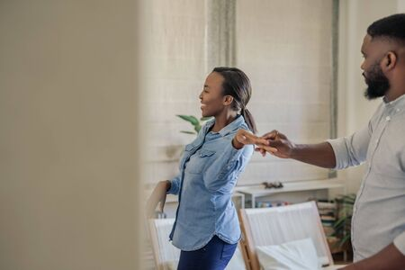 Laughing young African American couple dancing together at home